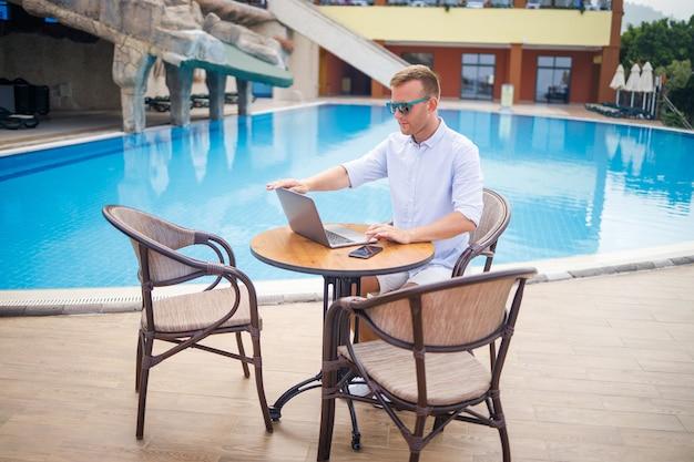 サングラスで成功したハンサムな男性実業家は、プールの近くに座っているラップトップで働いています。リモートワーク。フリーランサー