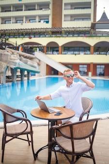 선글라스를 끼고 성공한 잘생긴 남성 사업가는 수영장 근처에 앉아 있는 노트북에서 일합니다. 원격 작업. 프리랜서