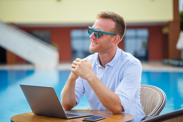 Successful handsome male businessman in sunglasses works at a laptop sitting near the pool. remote work. freelancer