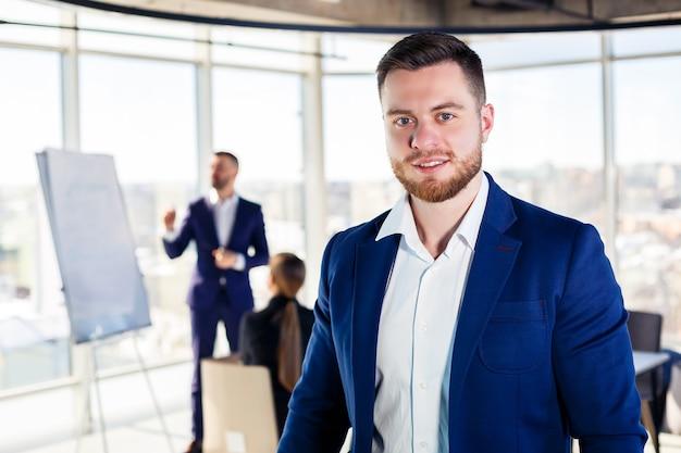 Успешный красивый мужской наставник, директор, бизнесмен в костюме в офисе. концепция рабочего дня. встреча команды с боссом на переднем плане