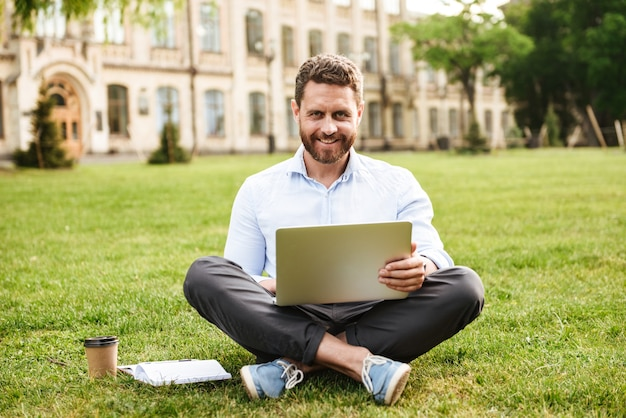 Successful handsome man in business clothing, sitting on ground with legs crossed and working on silver laptop while resting in park