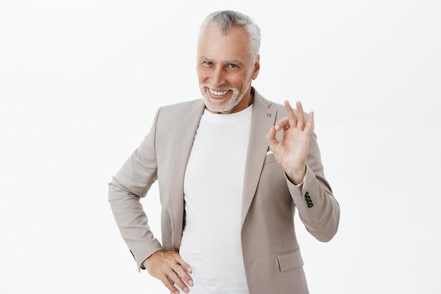 大丈夫なジェスチャーを示し、満足して笑顔を示す成功したハンサムなシニア男性起業家