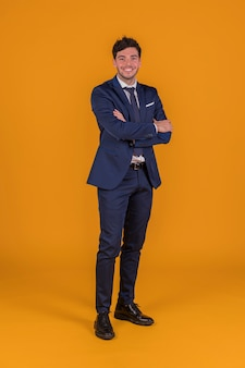 Successful handsome smiling young man with his arm crossed standing against an orange background