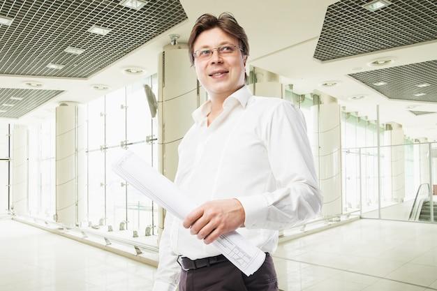 Успешный счастливый бизнесмен в офисе в белой рубашке с графиком в руке