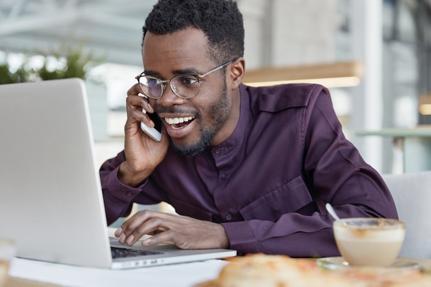 Successful happy dark skinned african male executive, smiles happily and looks at laptop computer