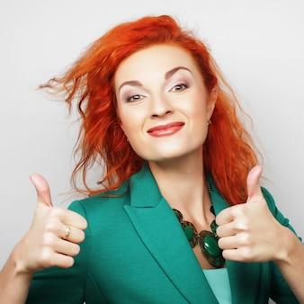 Успешная счастливая девушка дает большой палец вверх двумя руками