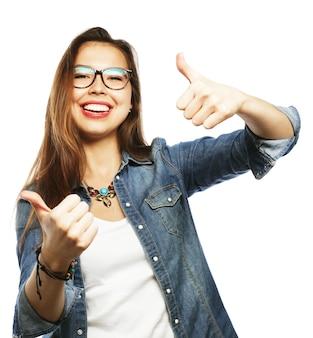 成功した幸せな女の子は両手で親指をあきらめる