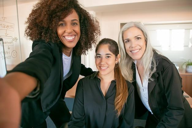 함께 사진을 위해 포즈를 취하는 성공적인 행복 사무실 팀. 자신감이 아름다운 경제인 또는 회의실에서 셀카를 복용 여성 관리자 미소. 팀워크, 비즈니스 및 관리 개념