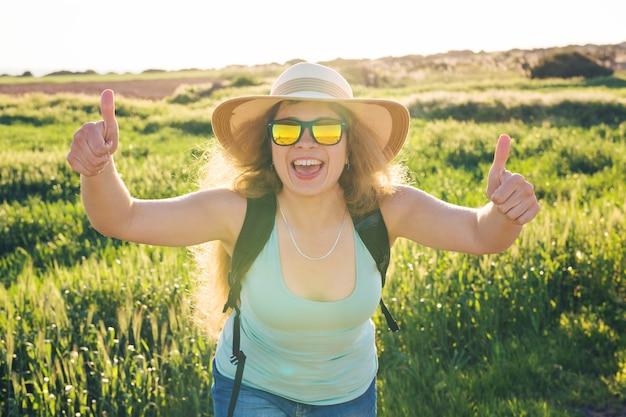 夏の畑で親指を立てるジェスチャーを承認する成功した幸せな女性
