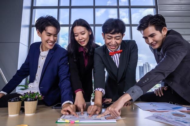 Успешные счастливые работники группа азиатских деловых партнеров разного пола (лгбт) видит и указывает на это при выполнении успешного бизнес-плана на сводном документе данных в комнате в офисе