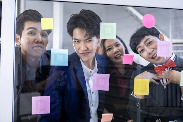 成功した幸せな労働者多様な性別を持つアジアのビジネスマンのグループ(lgbt)と付箋を使用してアイデアを共有します。ブレーンストーミングの概念。オフィスの会議室のガラスの壁に付箋