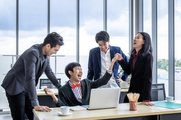 성공적인 행복한 노동자 다양한 성별(lgbt)을 가진 아시아 사업가 그룹이 손뼉을 치고 동성애 사업가에게 축하를 보냅니다. 노트북 컴퓨터에서 성공적인 사업 계획을 봅니다.