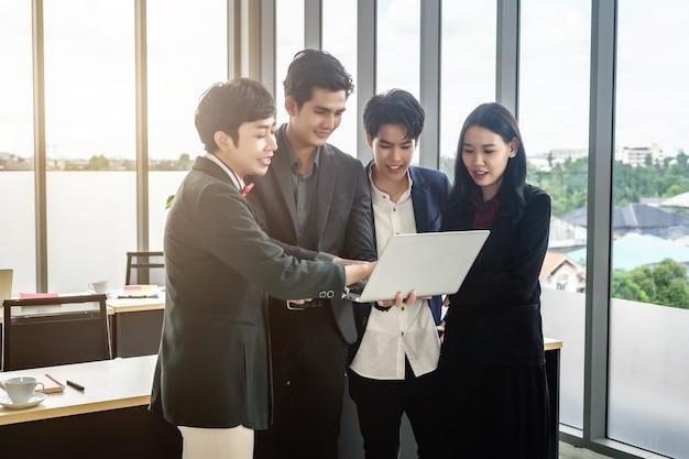 Успешные счастливые работники группа азиатских деловых людей разного пола (лгбт) видят успешный бизнес-план на портативном компьютере в конференц-зале в офисе