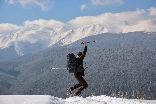 추운 겨울날 눈 덮인 산비탈을 걷고 있는 배낭을 메고 성공한 등산객.