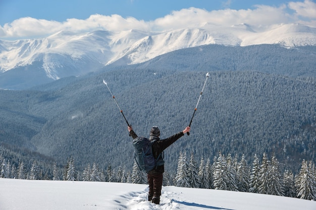 Successful hiker with backpack walking on snowy mountain hillside on cold winter day.