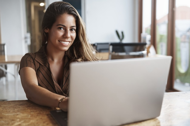 And successful hispanic woman smiling using laptop in cafe