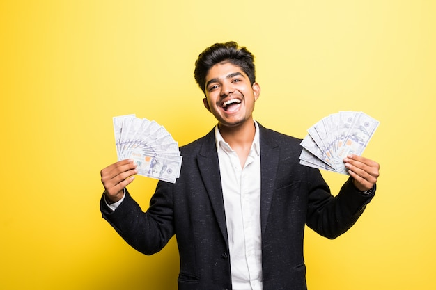 Successful indian entrepreneur with dollar banknotes in hand classical suit looking at camera with toothy smile while standing against yellow wall