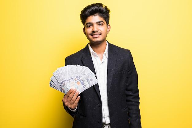 Успешный индийский предприниматель с долларовыми банкнотами в классическом костюме руки смотрит на камеру с зубастой улыбкой, стоя у желтой стены