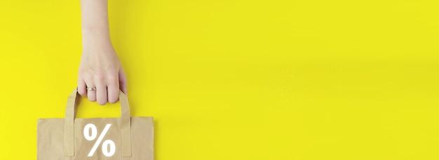 성공적인 국제 금융 투자 개념입니다. 노란색 배경에 홀로그램 이자율이 있는 재활용된 갈색 종이 쇼핑백이 평평하게 놓여 있습니다. 여름 판매 개념입니다.