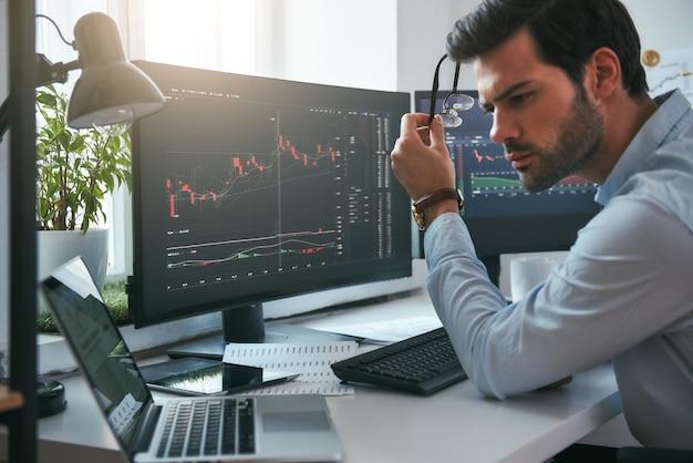 성공적인 투자자는 안경을 들고 데이터와 그래프를 분석하는 진지한 젊은 남성 상인