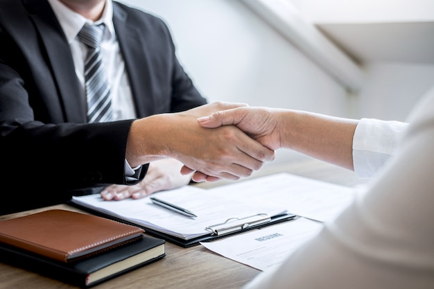Successful job interview, image of boss employer committee or recruiter in suit and new employee shaking hands after good deal negotiation interviewing, career and placement concept