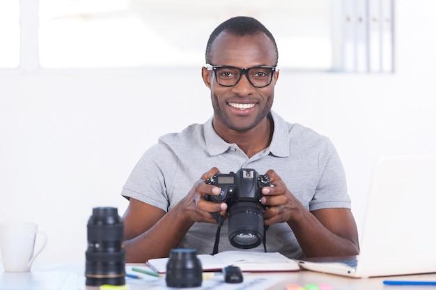 성공한 기자. 그의 작업 장소에 앉아서 카메라를 들고 캐주얼 복장에 잘 생긴 젊은 아프리카 남자