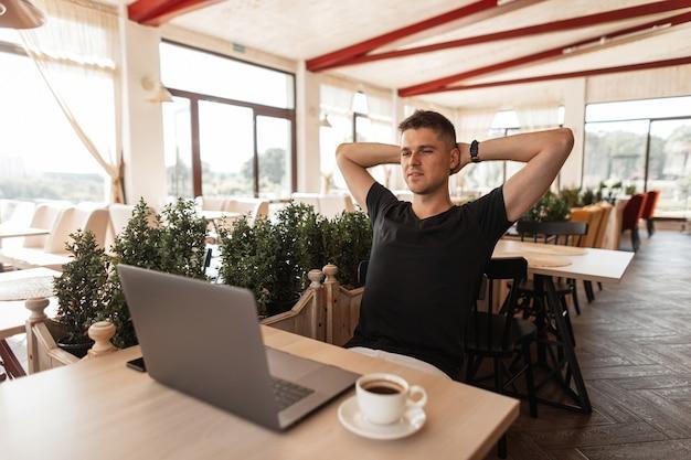 Успешный радостный молодой человек в черной футболке с компьютером сидит в современном кафе. счастливый парень фрилансер, работающий удаленно на ноутбуке. время расслабиться.