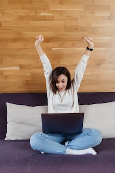 Successful lady is working on laptop computer sitting on dark bed in front of wooden wall at home