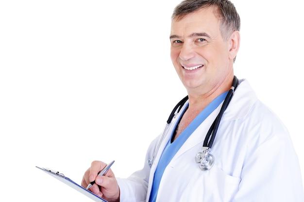 Medico maschio maturo di risata riuscito che scrive qualcosa