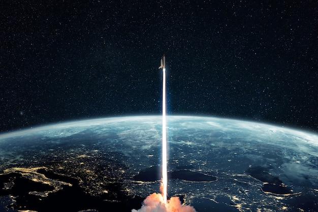 惑星地球から宇宙空間へのロケットの打ち上げに成功。スペースシャトルは、夜の街の明かりで惑星地球と星空の宇宙に飛び立ちます。宇宙船リフトオフの概念