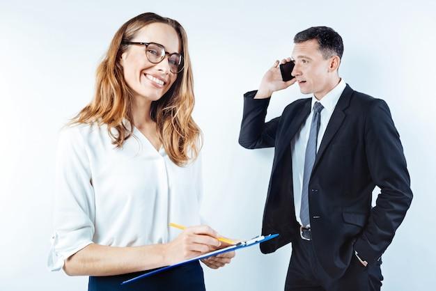 Удачная жизнь. снимок с пояса вверх: сияющая дама в очках что-то записывает, а ее коллега стоит позади и ведет серьезный телефонный разговор на заднем плане.