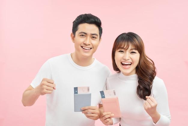 Успешная счастливая пара, получающая визу за границей, держа поднятый кулак, показывая паспорт с летающими билетами, крича с широко открытым ртом, изолированными на розовом фоне