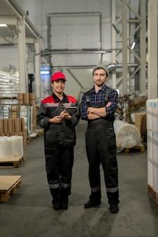 Успешные инженеры-мужчины и женщины большого современного завода стоят в проходе между штабелями упакованного сырья на складе.
