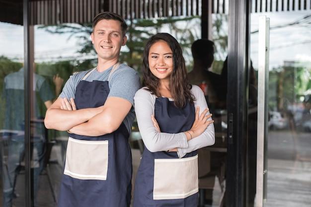 彼らのカフェやコーヒーショップの前に誇らしげに立っている成功した男性と女性の中小企業の所有者