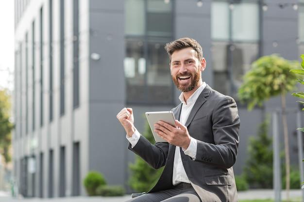성공한 남성 사업가는 좋은 승리 소식을 태블릿 컴퓨터에서 읽고, 승리와 성공에 대해 기뻐하고 감사합니다
