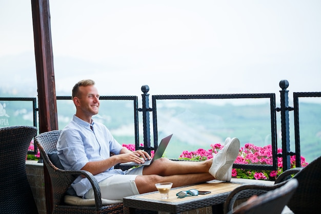 Успешный бизнесмен мужского пола, работающий в отпуске за ноутбуком с видом на горы. рабочий процесс онлайн-менеджера. работа на природе с прекрасным видом с балкона