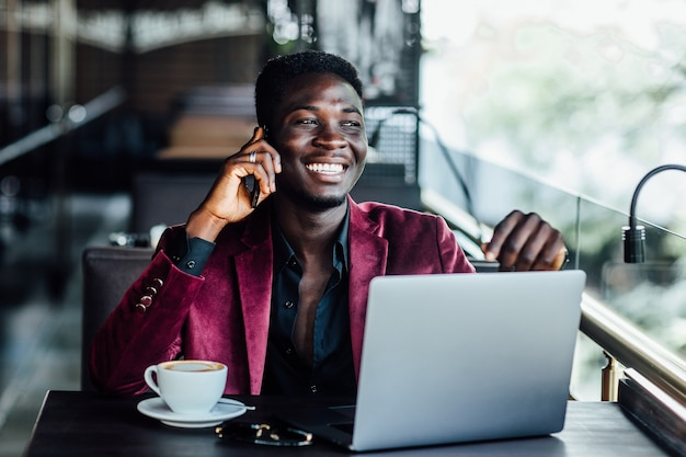 ラップトップを介してワイヤレスに接続する成功した男性のフリーランサー、思いやりのあるビジネスマンは、モダンなコーヒーショップのインテリアのテーブルに座ってネットブックに取り組んでいます。