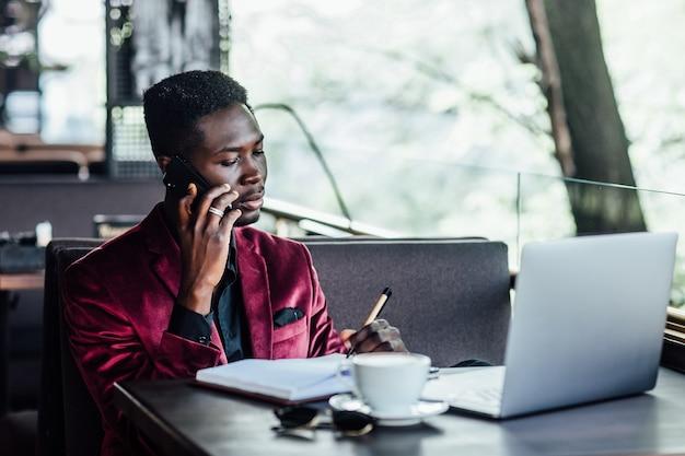 電話で話す成功した男性のフリーランサー、思いやりのあるビジネスマンはカフェテラスでネットブックに取り組んでいます。