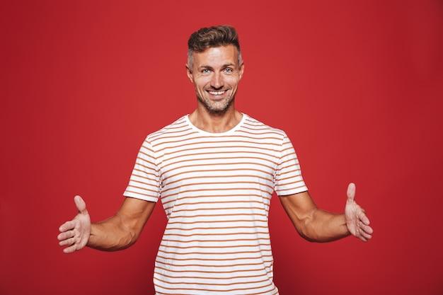 Успешный мужчина 30-х в полосатой футболке жестикулирует и демонстрирует размер с copyspace, изолированным на красном