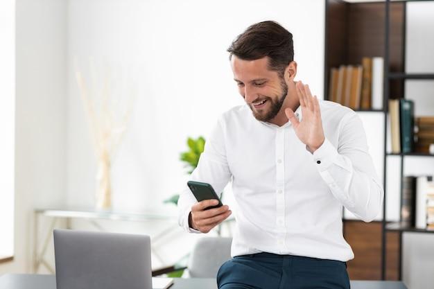 成功した男性、ceo、白いシャツを着たサラリーマンは、オフィスに立っている従業員やパートナーとのオンラインビデオ通話に携帯電話を使用しています