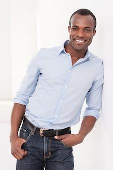 Успешный мужчина. веселый молодой темнокожий мужчина, прислонившись к стене и улыбаясь в камеру