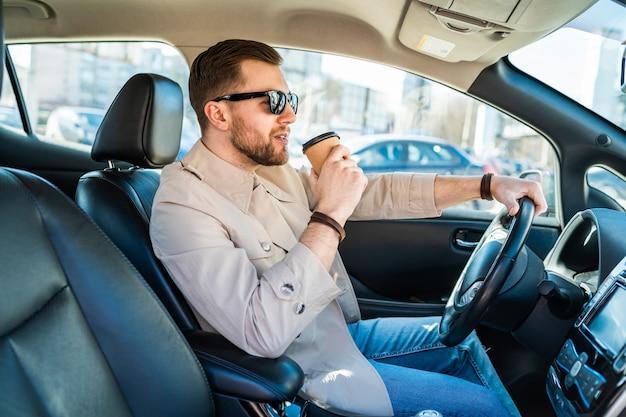 彼の手にコーヒーのカップで車を運転する成功した男