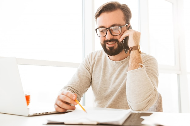 Successful man in eyeglasses running business from home workplace speaking on smartphone, and writing down notes on paper