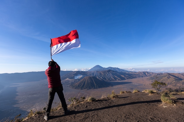 Successful man hiker taking picture with smartphone of volcano bromo indonesia.