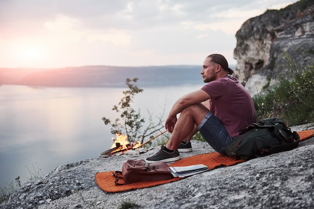 Successful man hiker on top of rock with campfire. freedom and active lifestyle concept