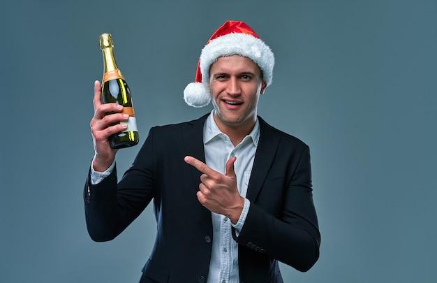 재킷과 크리스마스 모자를 쓴 성공한 남자는 새해를 축하하는 샴페인 한 병을 가리킵니다. 회색 배경에 스튜디오 사진입니다.