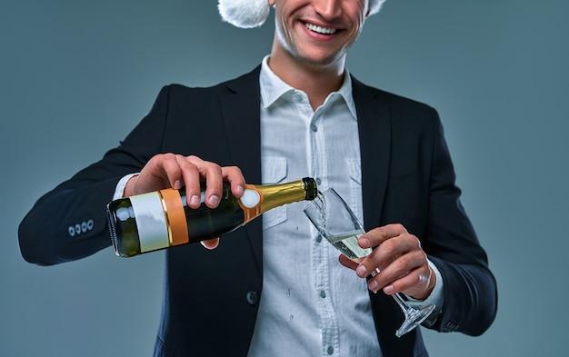 재킷과 크리스마스 모자를 쓴 성공한 남자는 새해를 축하하는 잔에 샴페인을 붓습니다. 회색 배경에 스튜디오 사진입니다.