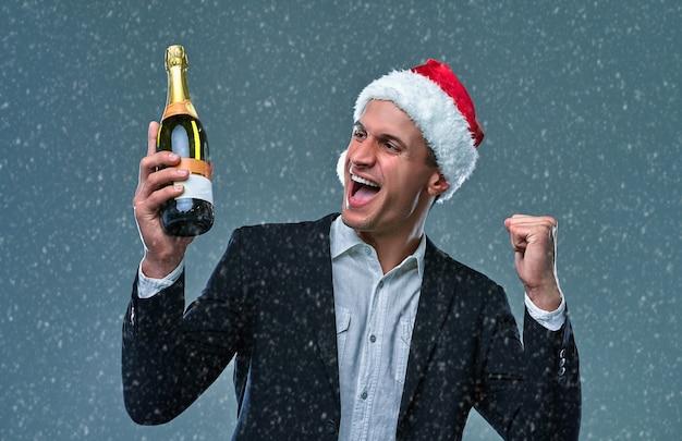 재킷과 크리스마스 모자를 쓰고 샴페인 한 병을 든 성공한 남자는 새해를 축하하고 예라고 말합니다. 회색 배경에 스튜디오 사진입니다.