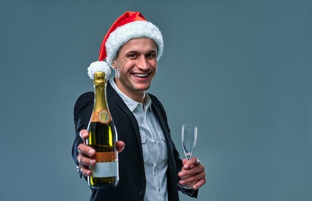 샴페인 한 병과 함께 재킷과 크리스마스 모자를 쓴 성공한 남자는 새해를 축하합니다. 회색 배경에 스튜디오 사진입니다.