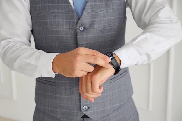 ベストで成功した男は彼の時計に触れます。